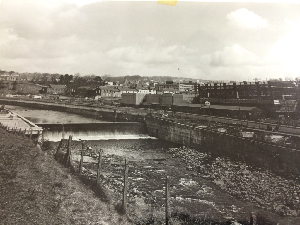 Looking North East across Merthyr Tydfil Town Centre, circa 1960's showing the St Tydfil's Link Bridge under construction across the Taff. The bridge was installed just below the weir. Image: by kind permission of St Tydfil's Shopping Centre Manager.