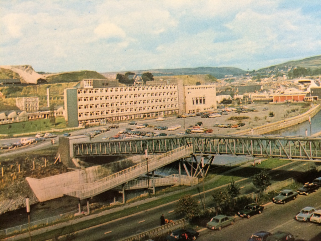 Postcard image looking North West across the Taff towards the FE College, circa late 1960's showing the now dismantled arm of the St Tydfil's Shopping Centre footbridge. Image: by kind permission of St Tydfil's Shopping Centre Manager.